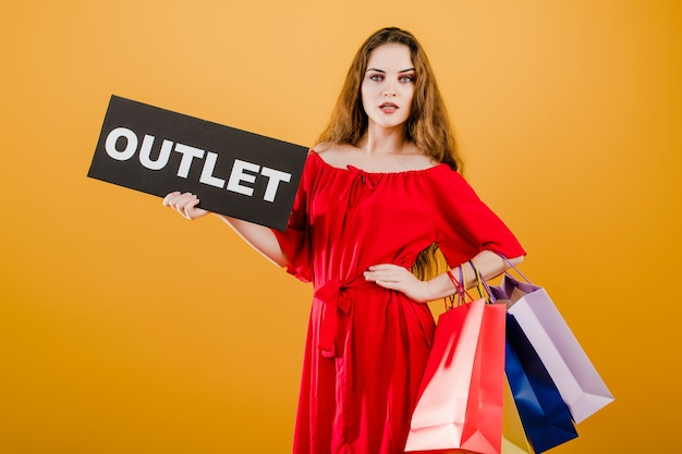 Beautiful woman has outlet sign with colorful shopping bags isolated over yellow