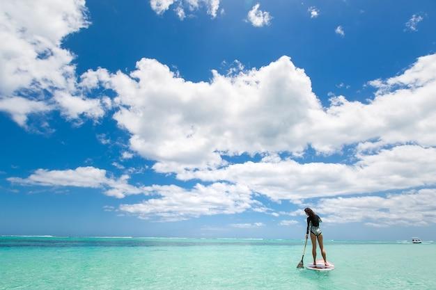 Красивая женщина занимается серфингом в прекрасный солнечный день