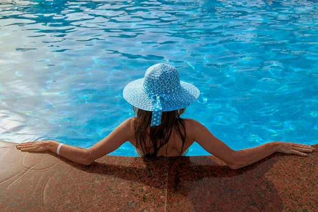 Beautiful woman in a hat sitting on the edge of the swimming pool summer in outdoors