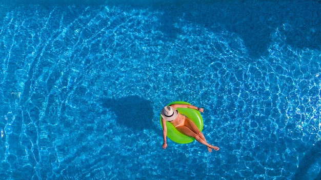 Beautiful woman in hat in swimming pool aerial view from above, young girl in bikini relaxes and swims on inflatable ring donut and has fun in water on vacation