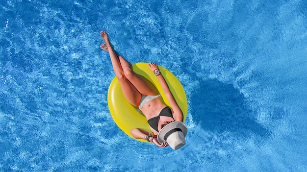 Beautiful woman in hat in swimming pool aerial view from above, young girl relaxes and has fun on inflatable ring