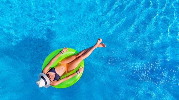 Beautiful woman in hat in swimming pool on inflatable ring in water on vacation