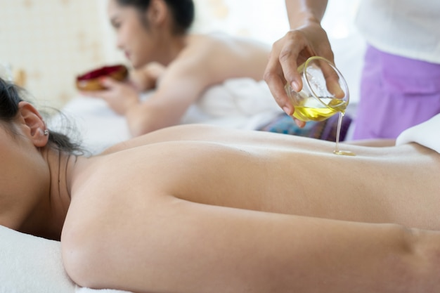 Красивая женщина с массажем спины и чувствует себя хорошо во время масляного массажа.