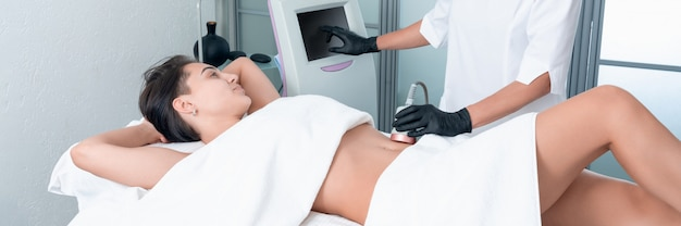 Beautiful woman having cavitation, procedure removing cellulite on legs and belly at beauty clinic