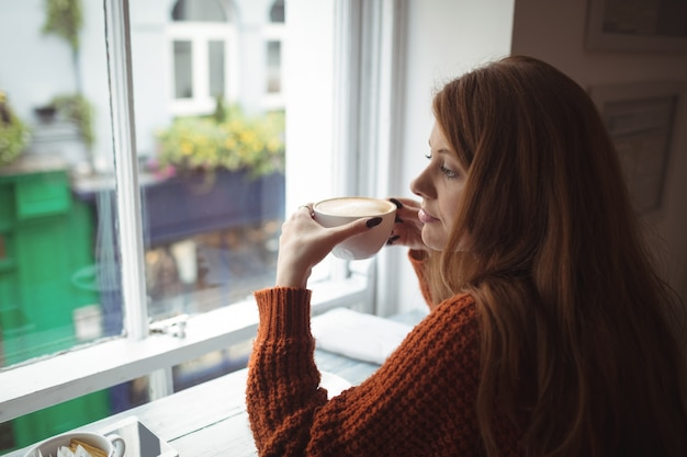 Bella donna che mangia caffè alla finestra