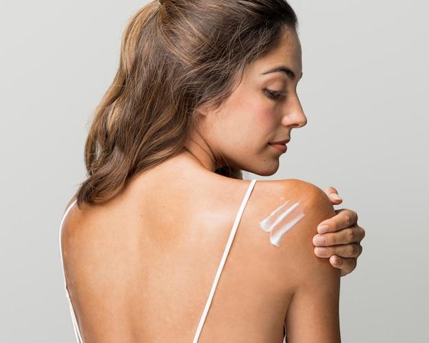 彼女の背中にクリームを持っている美しい女性