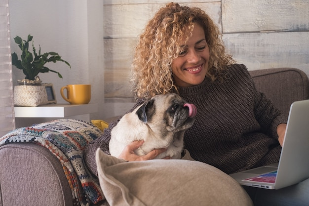 自宅のソファでノートパソコンを使用しながらペットの犬を楽しんでいる美しい女性。リビングルームのソファで彼女のかわいいペットの犬と一緒にラップトップで余暇を過ごす幸せな女性