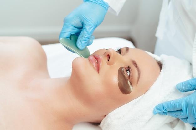 미용사가 하는 구아샤 스크레이퍼 얼굴 마사지를 받는 아름다운 여성