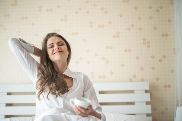 Bella donna nella sua camera da letto bere caffè al mattino