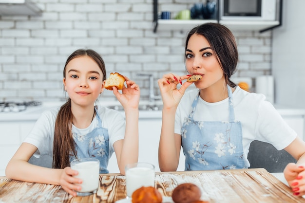 Beautiful woman and her cute little daughter in aprons are looking at front while tasting cupcakes