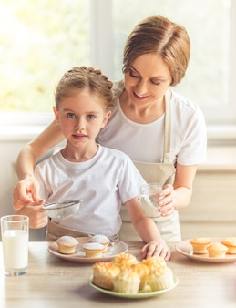 Beautiful woman and her cute little daughter in aprons.