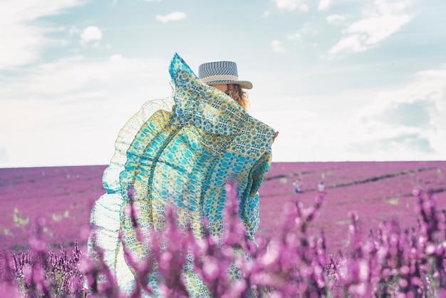 ラベンダー畑でドレスの後ろに隠れている美しい女性。美しい花壇や新鮮なラベンダーの花のフィールドで彼女の休日を楽しんでいる帽子の女性