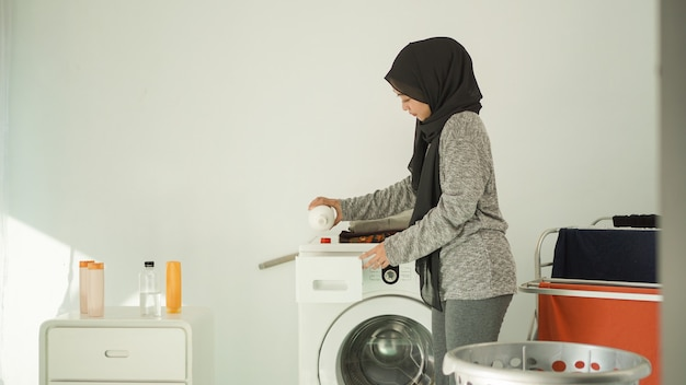 Beautiful woman in hijab pours detergent for her laundry at home