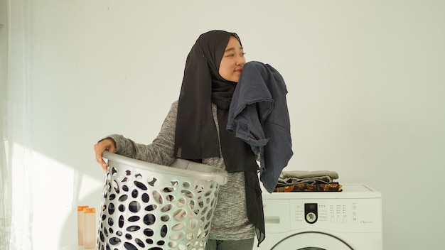 Beautiful woman in hijab smells the fragrance of clothes at home
