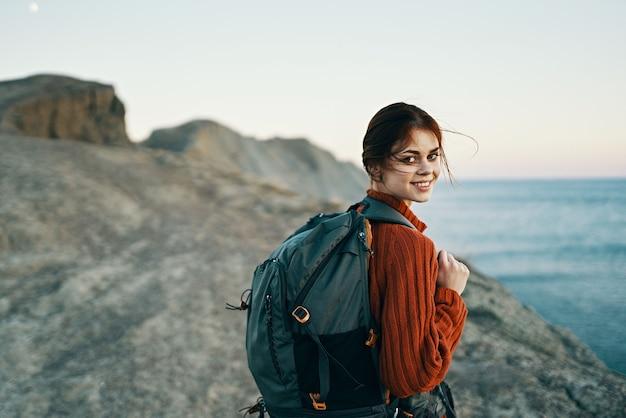 海の風景モデルの近くの山で彼女の背中にバックパックを持つ美しい女性ハイカー