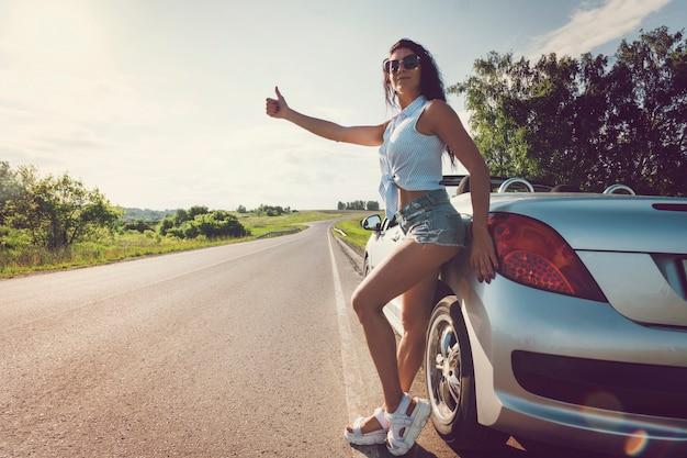 壊れた車でヒッチハイクする美女。ショートパンツの美しい若いセクシーな女の子が彼女のコンバーチブルに立っています。道路上の車の問題。ガスがなくなった。