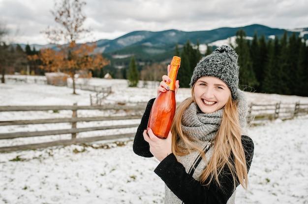 Красивая женщина держит бутылку шампанского на фоне зимних гор. девушка снежной зимой, прогулка на природе. концепция путешествий и отдыха. праздники зимнего сезона.