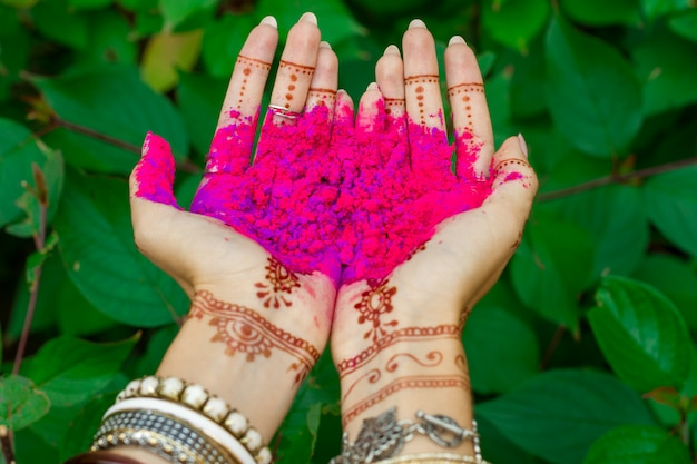 Beautiful woman hold in hands with henna tattoo and bracelets jewelry colorful pink violet holi dust powder paint happy traditional indian wedding, holiday summer culture festival concept green leaves