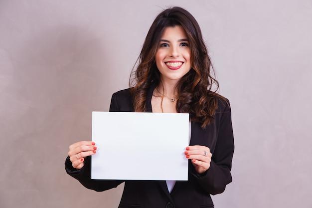 白い背景で隔離の空白の看板を保持している美しい女性