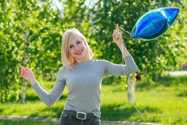 푸른 잔디와 나무를 배경으로 공원에서 파란 풍선을 들고 있는 아름다운 여성