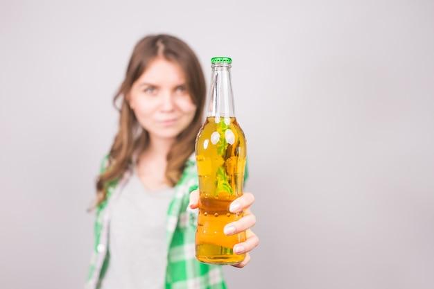 ビールの瓶を持ち、親指を立てる美しい女性。コピー スペースの背景。
