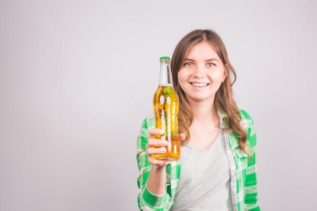 ビールの瓶を持った美しい女性。コピー スペースの背景。