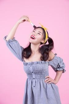 ピンクの背景にブラシをかけたブラシを保持している美しい女性。