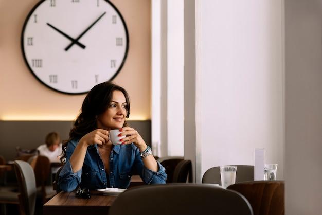 コーヒーショップで一杯のコーヒーを保持している美しい女性。