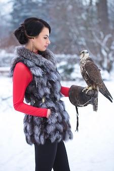 Красивая женщина, держащая сокола на руке зимой