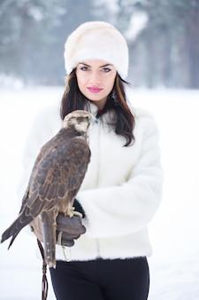 겨울에 그녀의 손에 매를 들고 아름 다운 여자