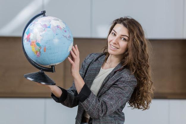 地球儀を手に持って、笑顔の美しい女性がオフィスにいます