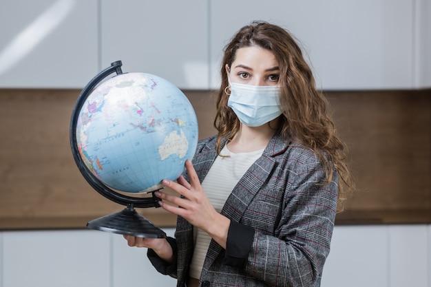 彼女の手に地球儀を持って、彼女の顔に保護医療マスクを身に着けている美しい女性