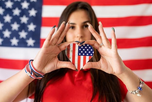 미국 국기 배경에 작은 국기를 들고 아름 다운 여자