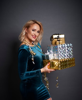 贈り物のスタックを保持している美しい女性