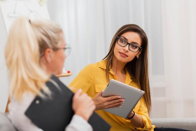 Красивая женщина держит планшет и смотрит на своего коллегу