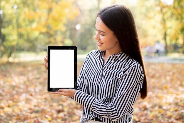 Красивая женщина держит планшет с макетом