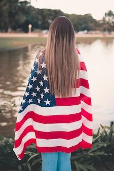 Beautiful woman holding american flag - image