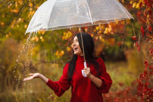 Красивая женщина держит зонтик под дождем и улыбается