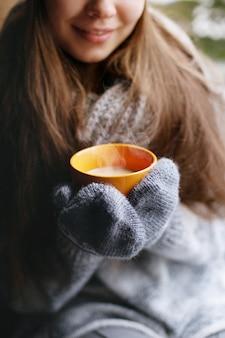 아름 다운 여자를 창가 집에 앉아 장갑에 커피 또는 코코아 한 잔을 마시는. 흐리게 겨울 눈 나무 배경입니다.
