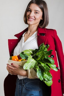 Beautiful woman holding bag with organic vegetables