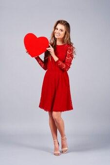 Bella donna che tiene un grande cuore rosso red