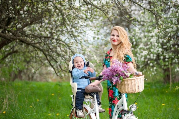 Beautiful woman holding bike and happy baby sitting in bicycle chair in the basket lay a bouquet of lilacs