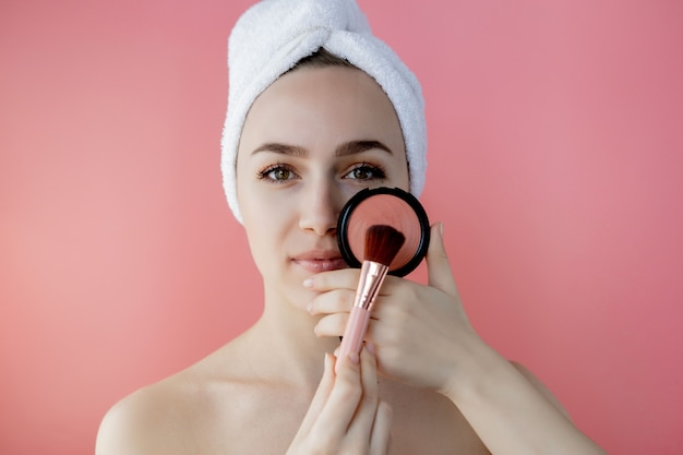 Beautiful woman holding blush brush to apply blush on cheeks on pink background