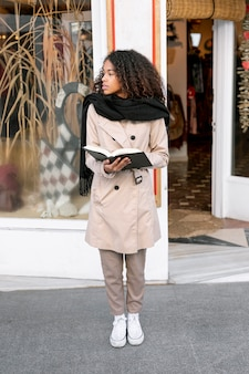 Beautiful woman holding a book outside