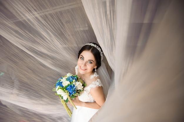 Beautiful woman holding a bouquet of flowers wearing in luxurious wedding dress.