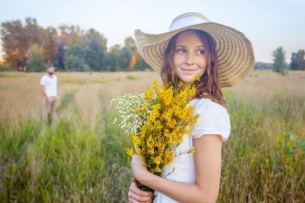 노란 꽃 꽃다발을 들고 배경에 있는 남자친구와 함께 카메라를 바라보는 아름다운 여성.