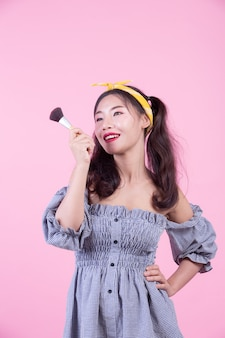Beautiful woman holding a brush, brushed on a pink background.