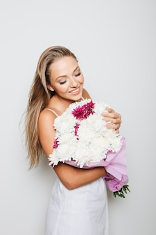 Beautiful woman holding bunch of flowers