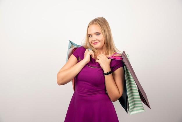 ショッピングバッグの束を保持している美しい女性。