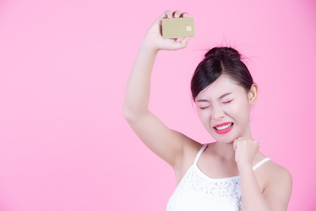 Beautiful woman holding a card on a pink background.